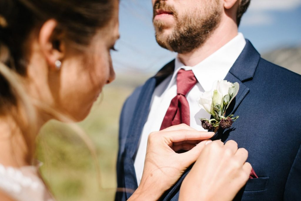 bride pinning the boutonniere on the lapel of the groom