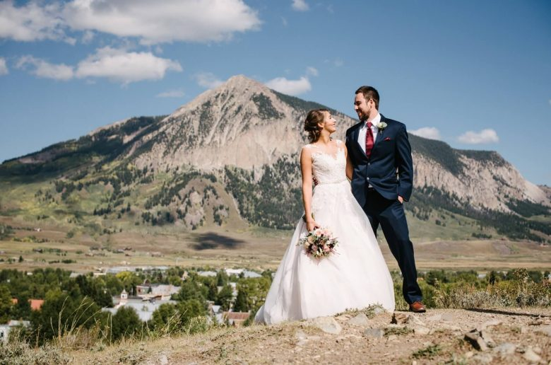 bride in a lace dress and groom wearing Michael Kors Navy Sterling Wedding Suit