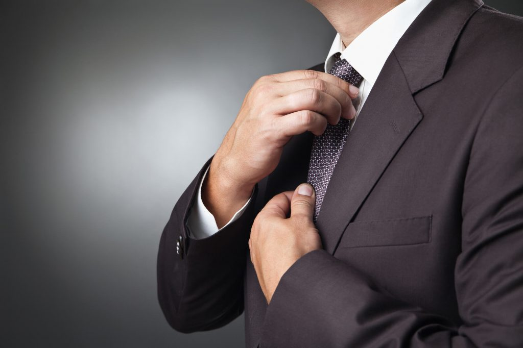 adjusting tie while showing off lapel