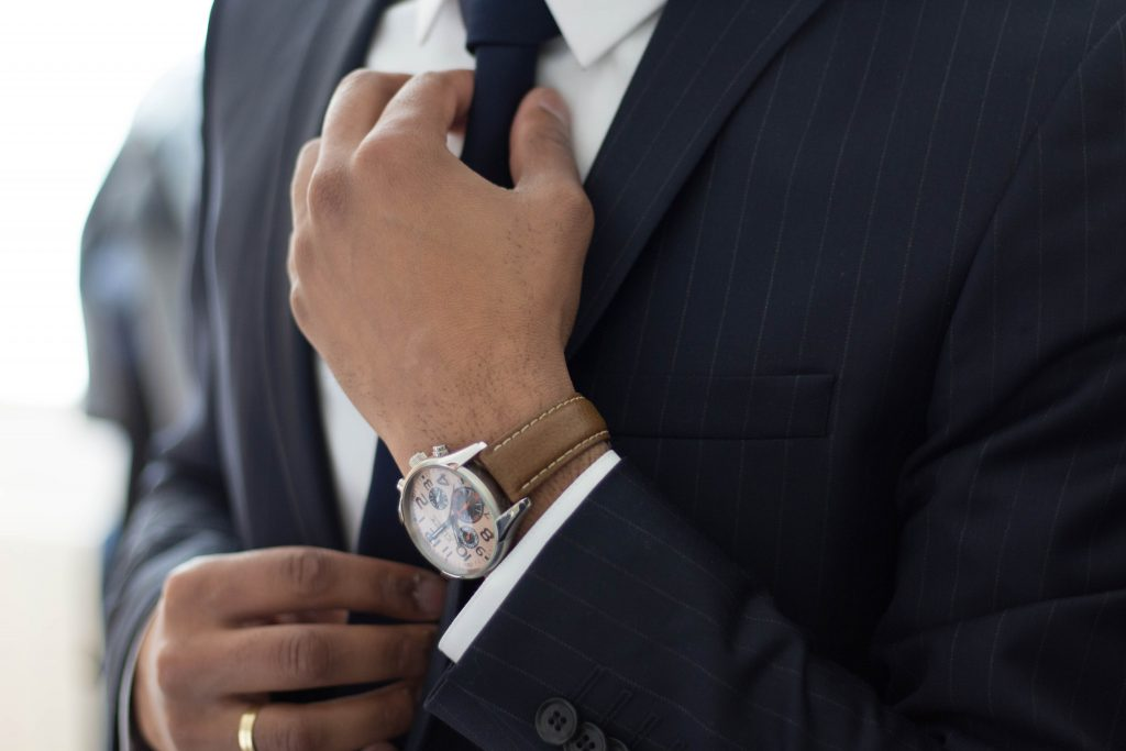 When to Wear a suit to an interview - Man adjusting his tie in a business suit