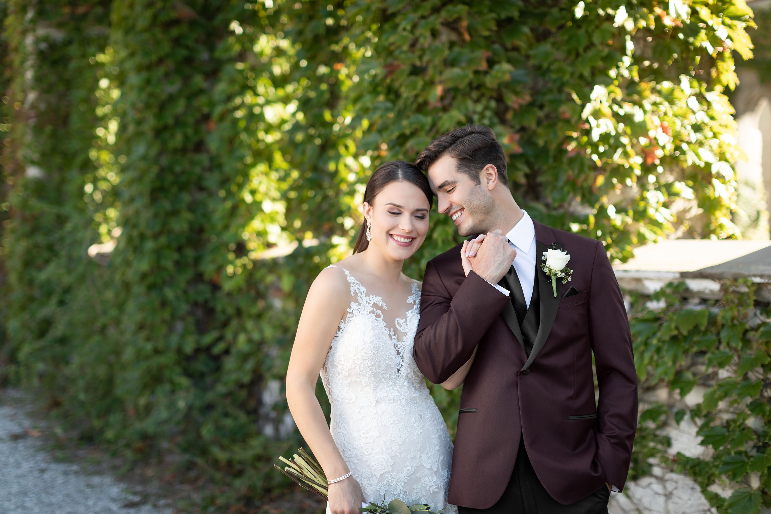 Bride and Groom smiling in front of vines , Groom is wearing a Custom Tuxedo