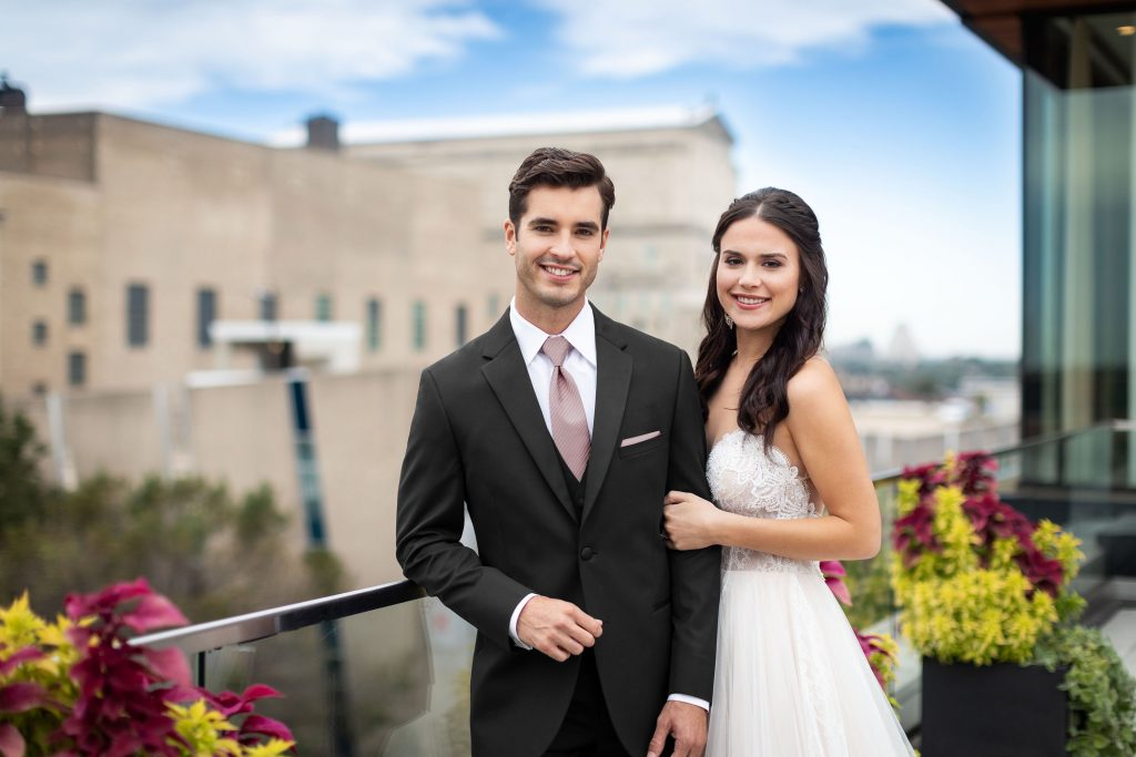 Bride and groom smiling on a balcony, groom is wearing a legacy performance tuxedo - Your Guide to a custom tuxedo
