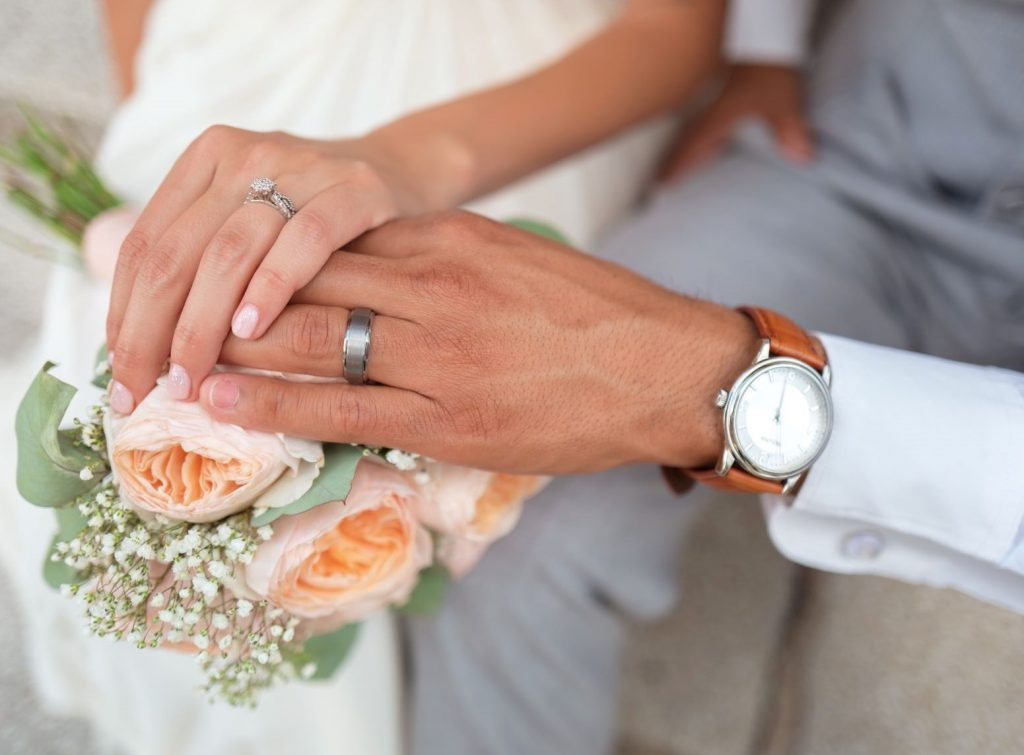 Ultimate Wedding Checklist for Grooms - Married Couple holding hands with wedding rings