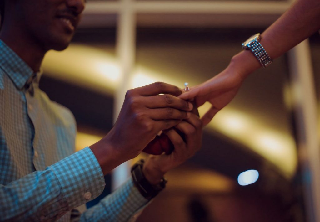Ultimate Wedding Checklist for Grooms - Proposal shot of man putting a ring on a woman's finger