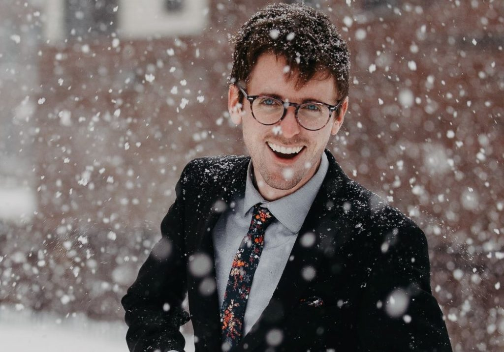 Men's Holiday Style Guide - A man dressed in a suit standing in the snow