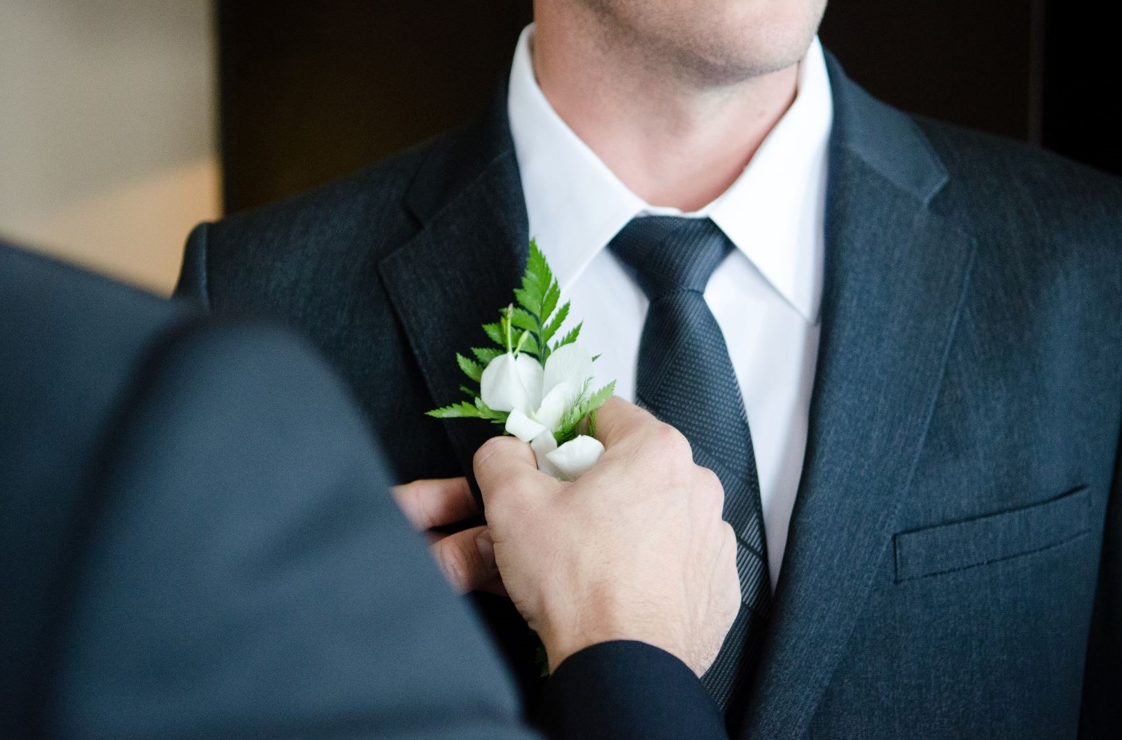 How to wear a boutonniere - Friend helping attach a boutonniere to a suit