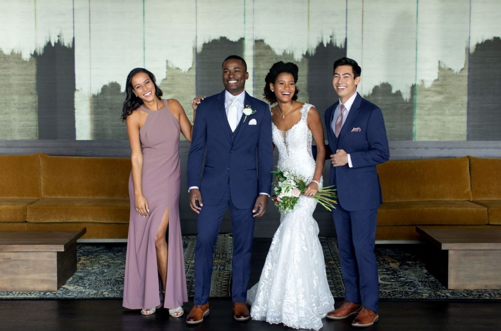 What to wear to a spring wedding - Men in blue suits, bride, bridesmaid in pink