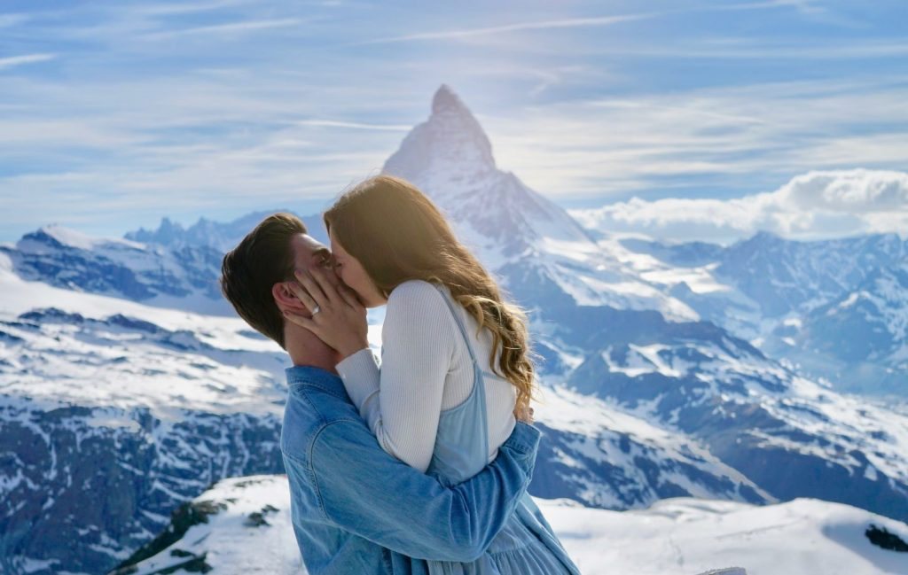 Creative Proposal Ideas - Man holding up women in front of a snowy mountain