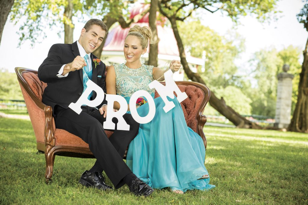 Best Promposal Ideas - Couple sitting on a bench with a prom sign