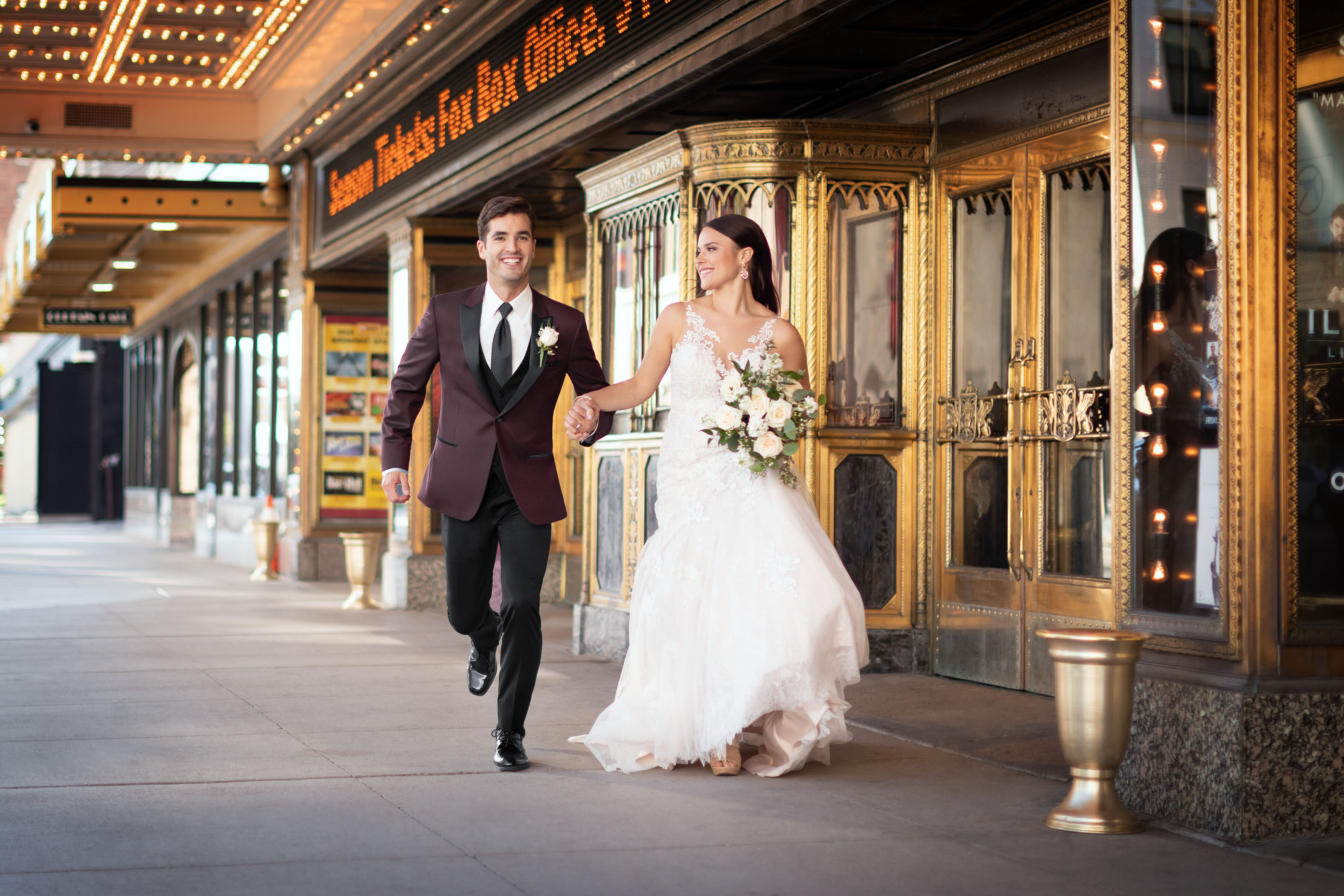 fall wedding colors -bride running with groom wearing burgundy jacket and black pants