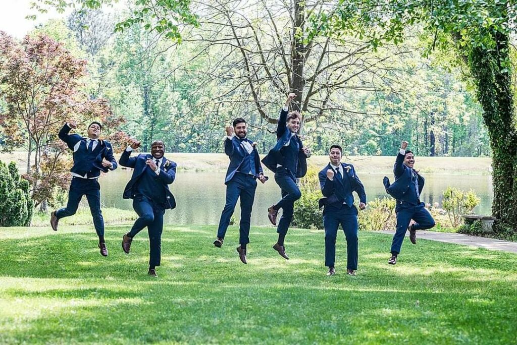 groom and groomsmen in blue suits jumping for joy