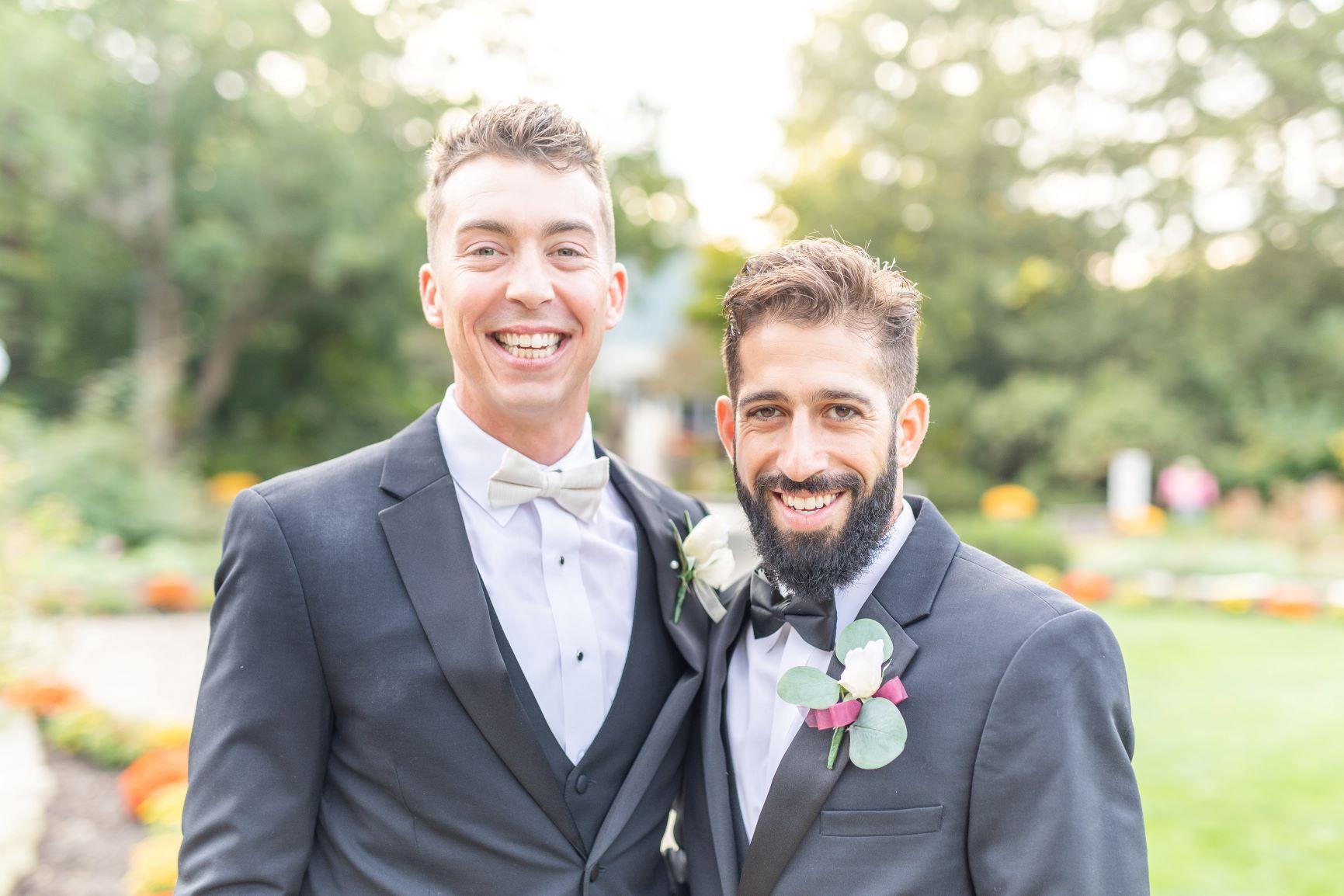 groom standing next to his groomsman wearing matching black tuxedos