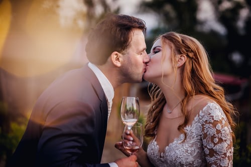 bride and groom kissing with glass of wine