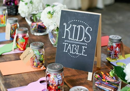entertain kids at wedding - Kids table at wedding with chalkboard sign, crayons, candy