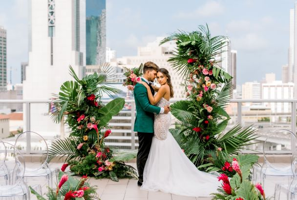 groom in green jacket with bride infront of tropical flowers