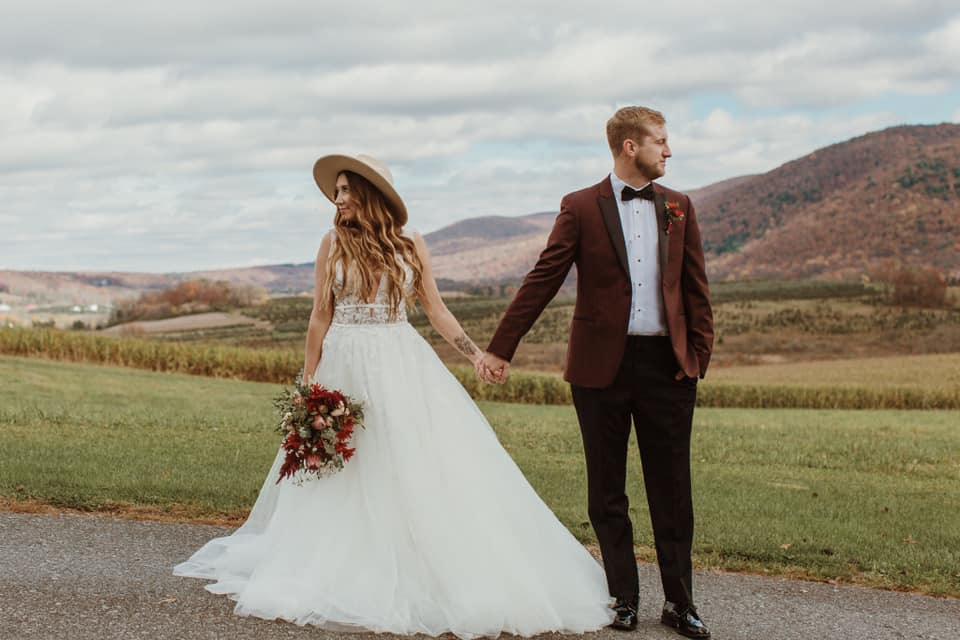 bride in bridal gown with hat and groom in burgundy tux jacket