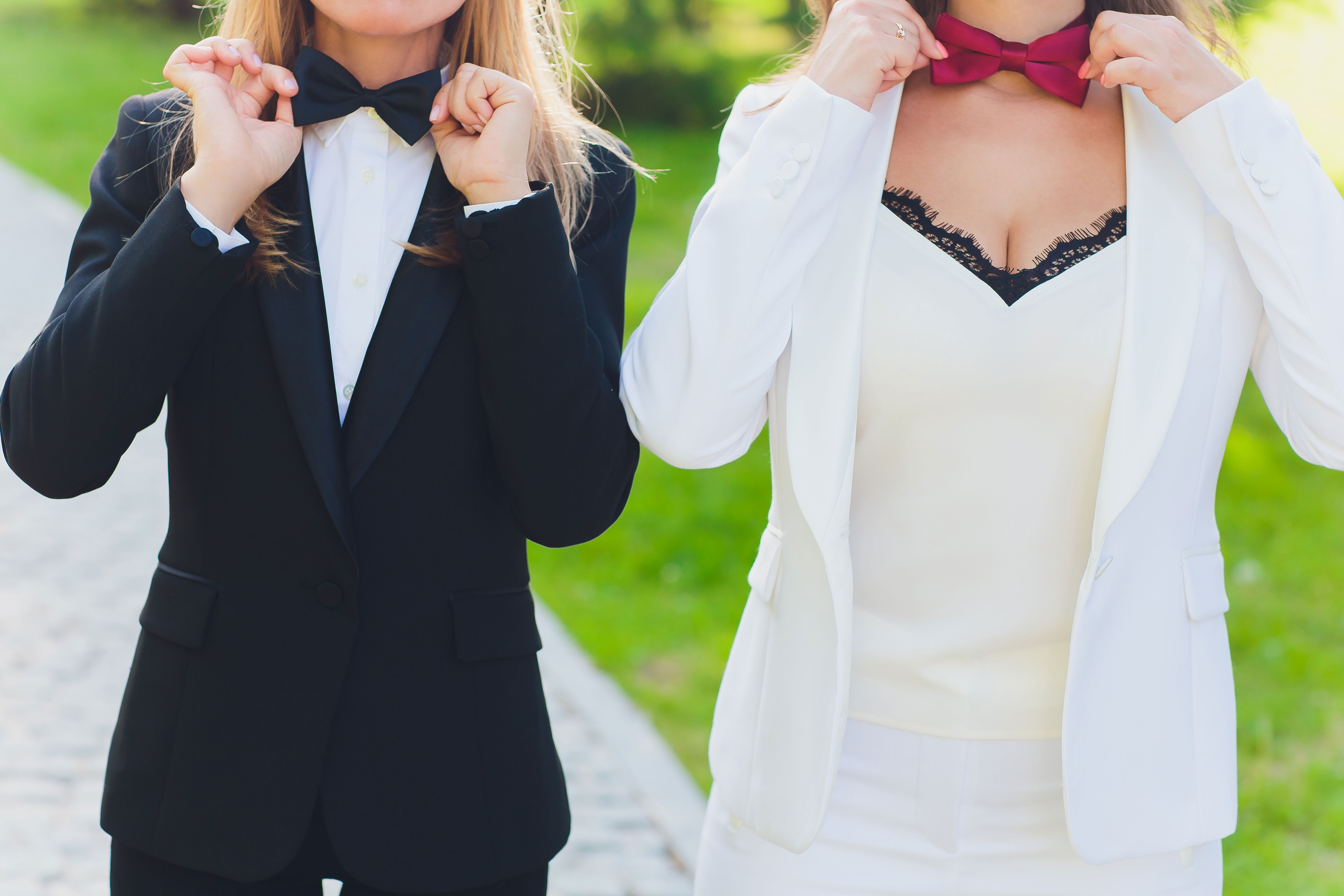 one woman in black tux with black bow tie and another woman in white tux with red bow tie