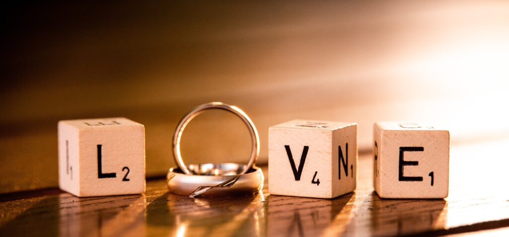 letter blocks spelling love with wedding rings - wedding insurance