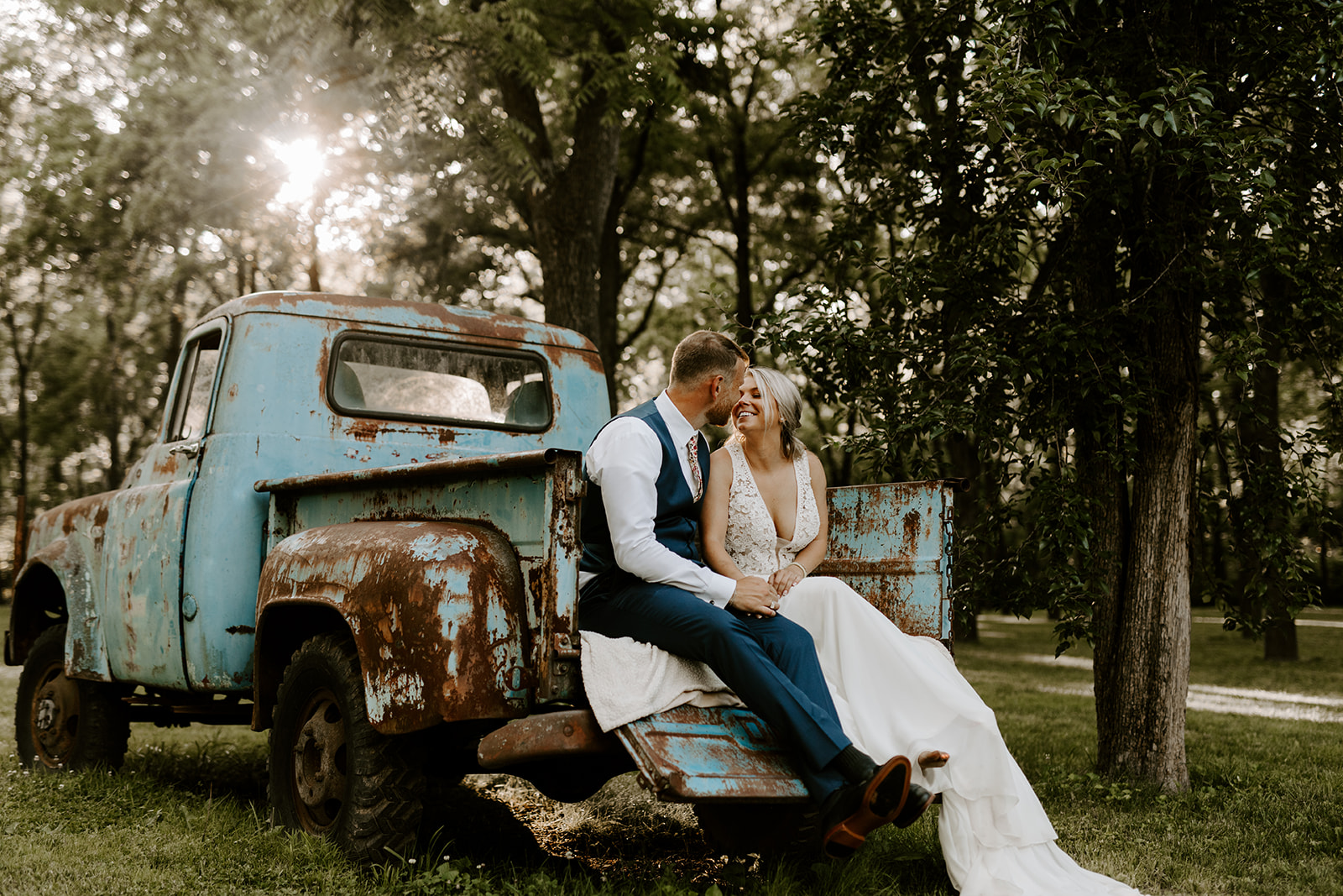tasks to delegate - bride and groom sharing a moment on the back of an old truck
