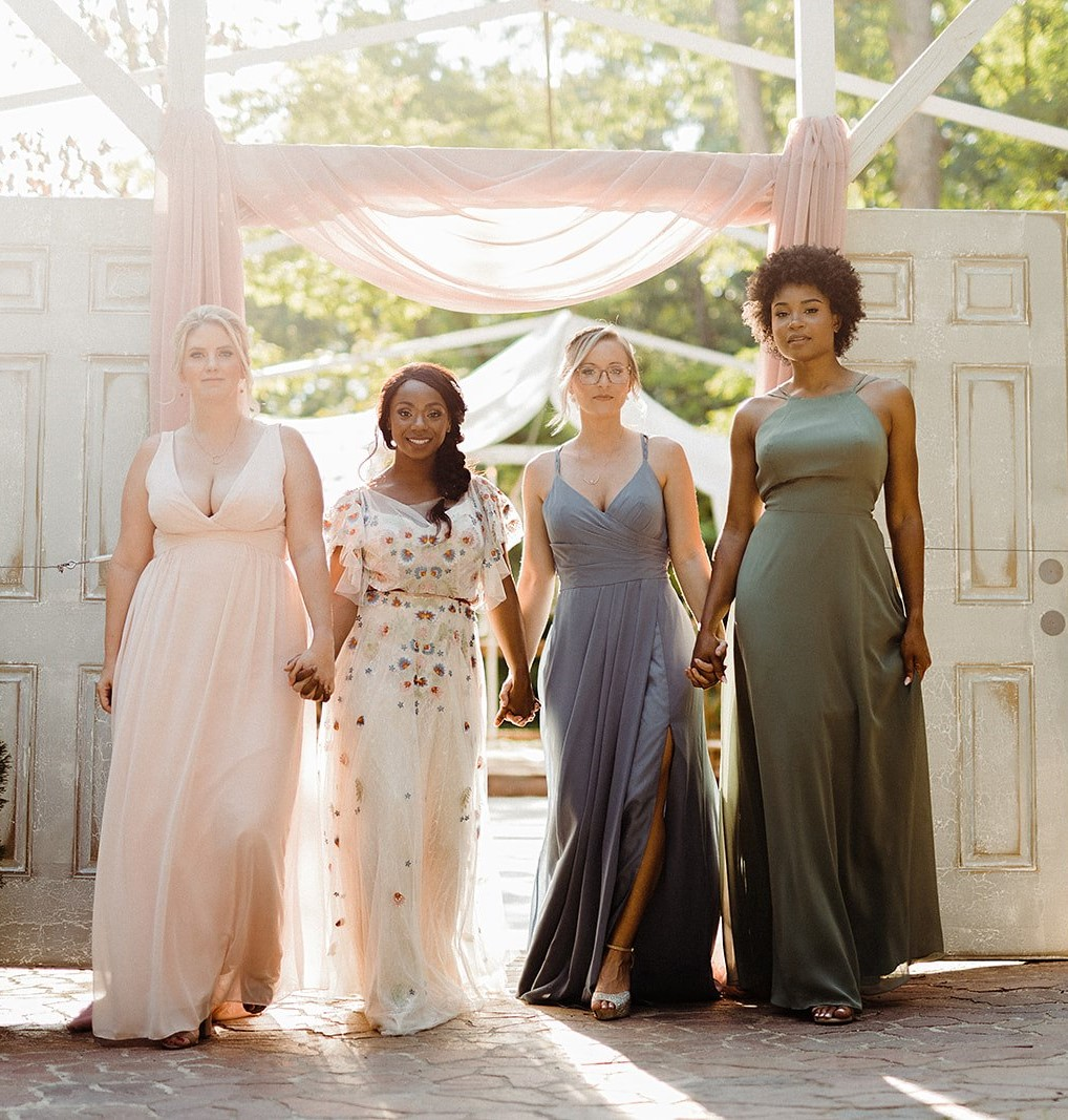 women in different colored dresses that match spring wedding colors; light pink, dusty blue, sage green and white with multi colored flowers