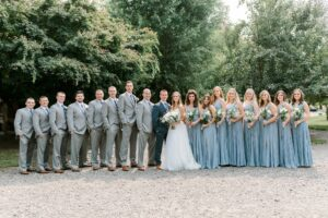 bride and groom with wedding party, groomsmen in grey suits, bridesmaids in dusty blue dresses