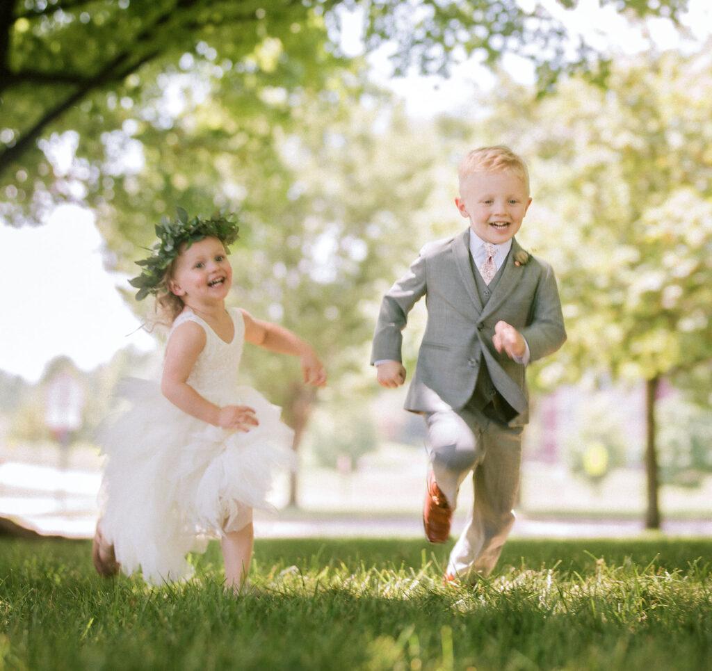tasks to delegate on your wedding - ringbearer and flower girl running outside