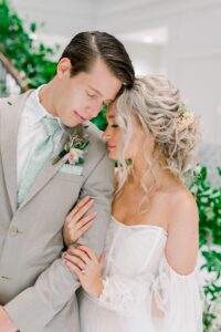 groom in sand colored wedding suit with floral sage green tie standing next to bride in wedding dress