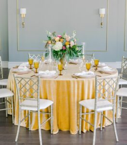 table with yellow table cloth, two charis, flower arrangement
