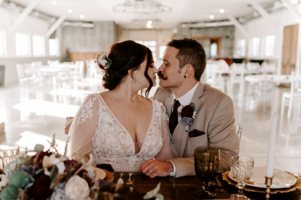 when should I rent a tuxedo - bride and groom kissing in reception hall