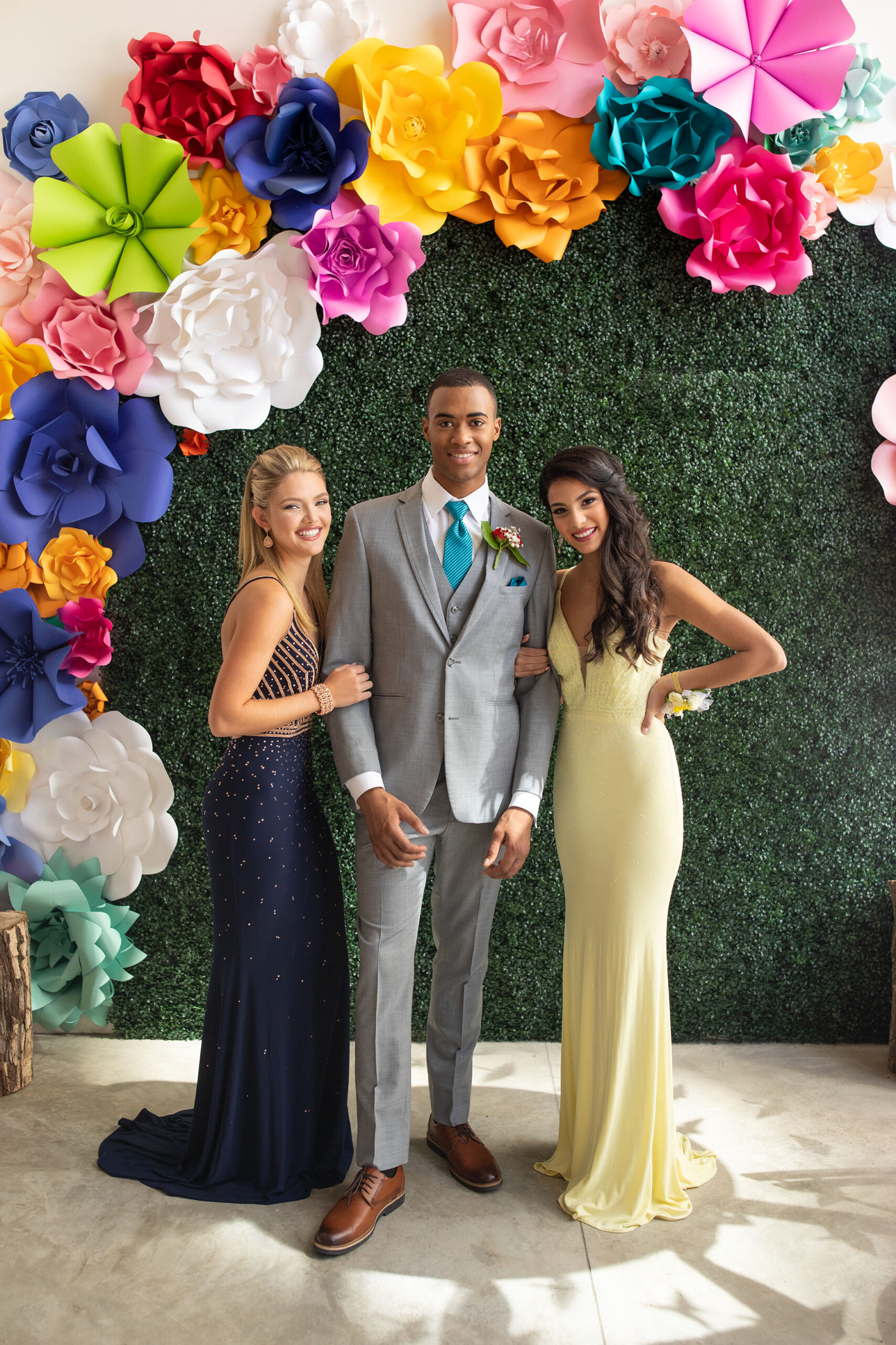 prom after-party picture with guy in grey suit, blonde female in navy dress and brunette in yellow dress standing in front of moss covered wall with brightly colored paper flowers