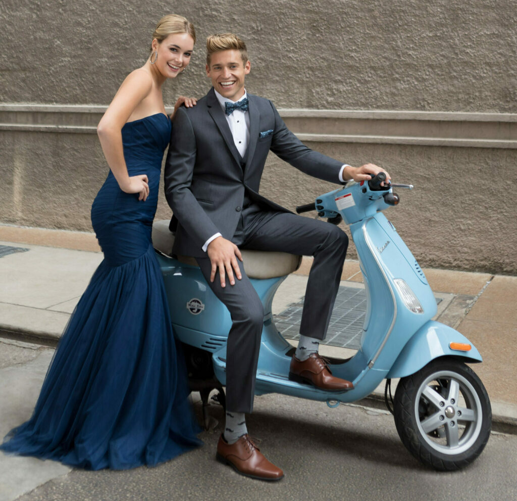 save money on prom with alternate transportation - prom guy in grey suit and prom girl in navy dress arrive on a Vespa scooter
