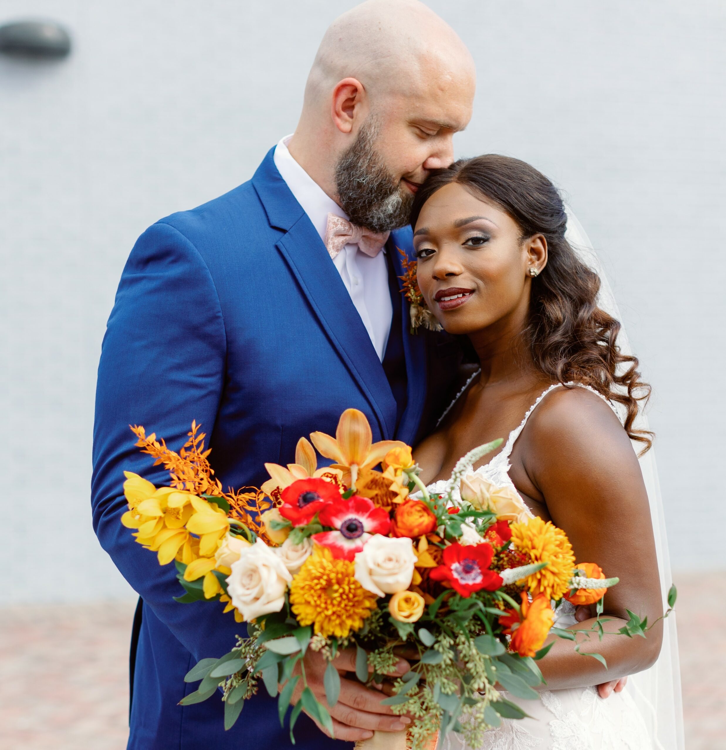 black bride in white dress holding colorful bouquet while standing next to white groom in blue suit