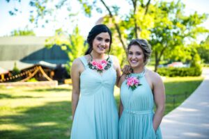 bridesmaids in mint gren dress and floral necklaces at a summer wedding