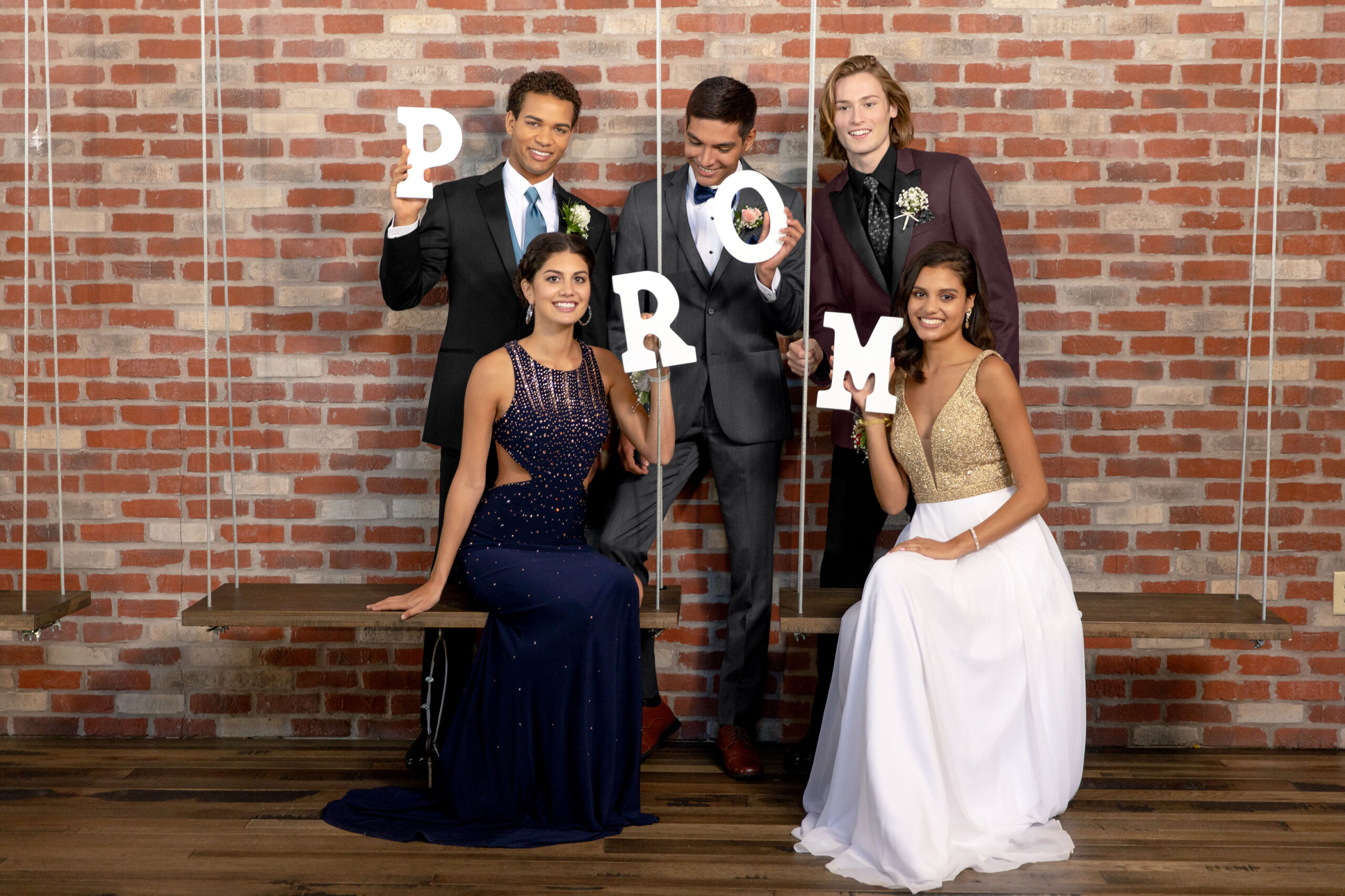 save money on prom - group of five prom kids with the guys in colorful tuxedos and the girls sitting on swings in front of them holding the letter P, R, O, M to spell prom