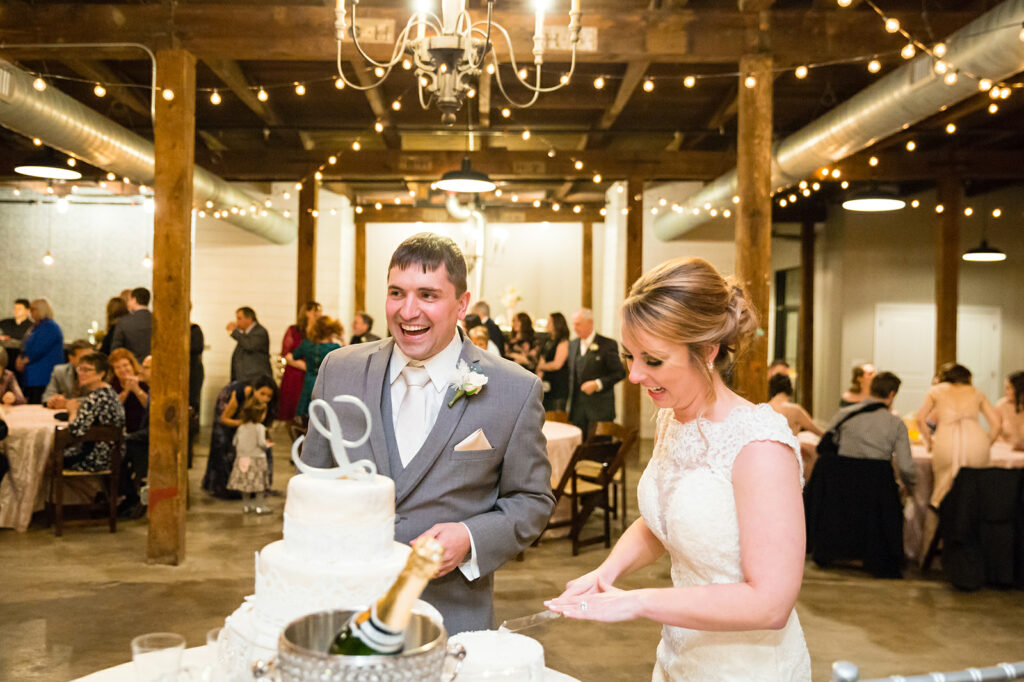 anniversary reception - groom in grey tuxedo standing next to bride wearing lace dress cutting the three tier wedding cake with their guests watching in the background