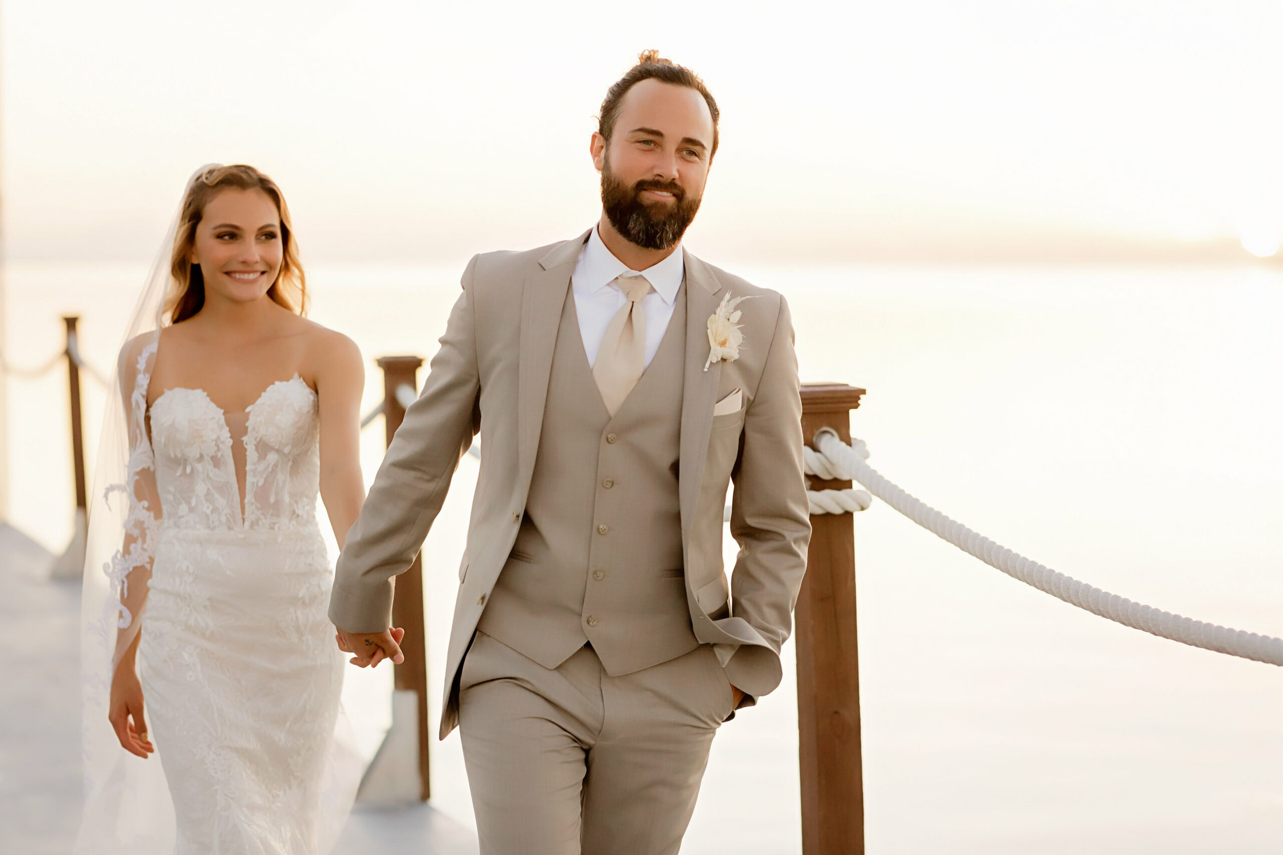 bride and groom wearing tan suit walking along a peer on the waterfront hand in hand