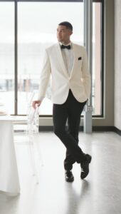 man in ivory shawl dinner jacket and black pants standing next to chair