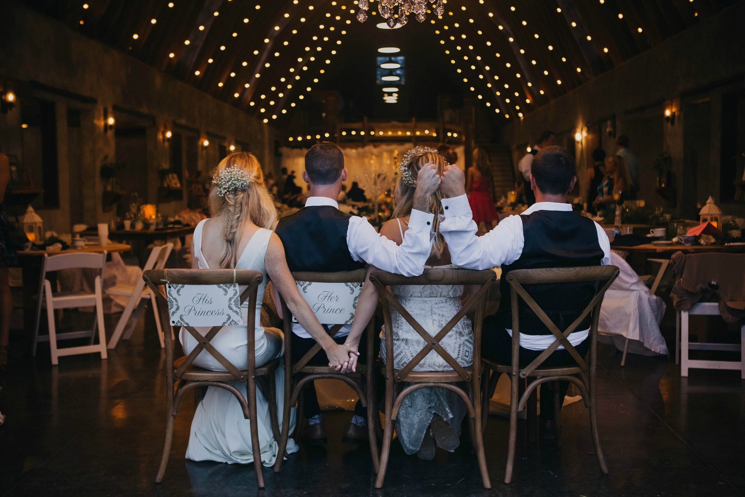 bride, groom, maid of honor, best man sit with their backs facing us and the reception in the background. Bride and bridesmaid hold hands as the men fist pump.
