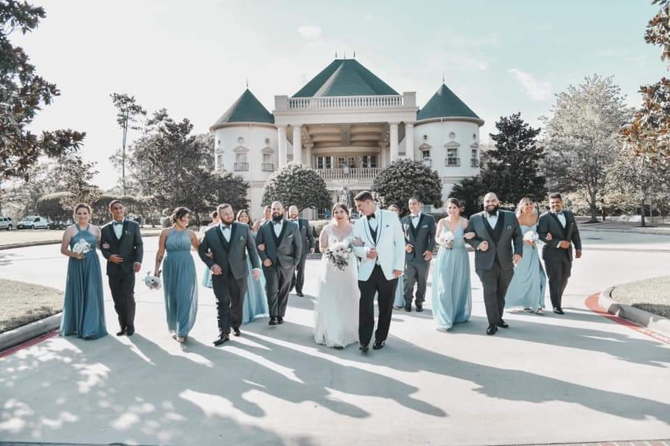 wedding party walking with a majectic building in the background. Groomsmen wearing dark grey tuxedos with groom in a white tuxedo coat and black pants. Bridesmaids in various shades of green dresses.