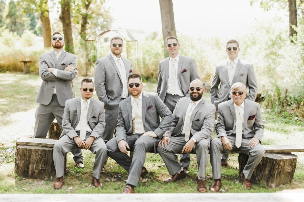 groom and groomsmen pose with sunglasses surrounded by trees. Groom in dark grey suit with groomsmen with a lighter shade of grey.