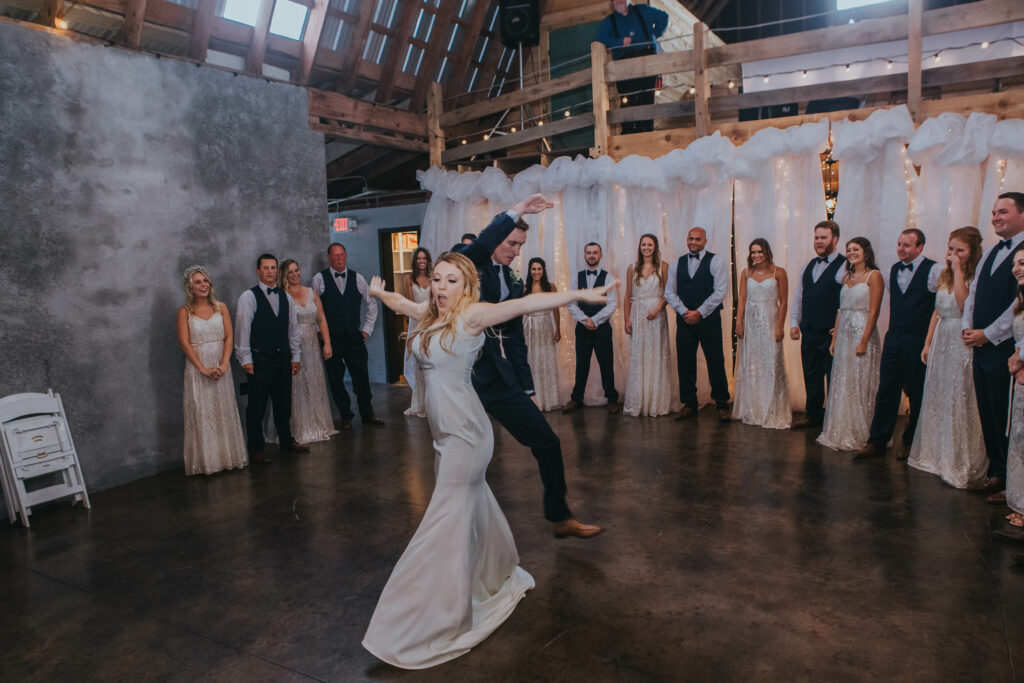 bride in silk dress and groom in navy suit dance together as bridal party circle around them