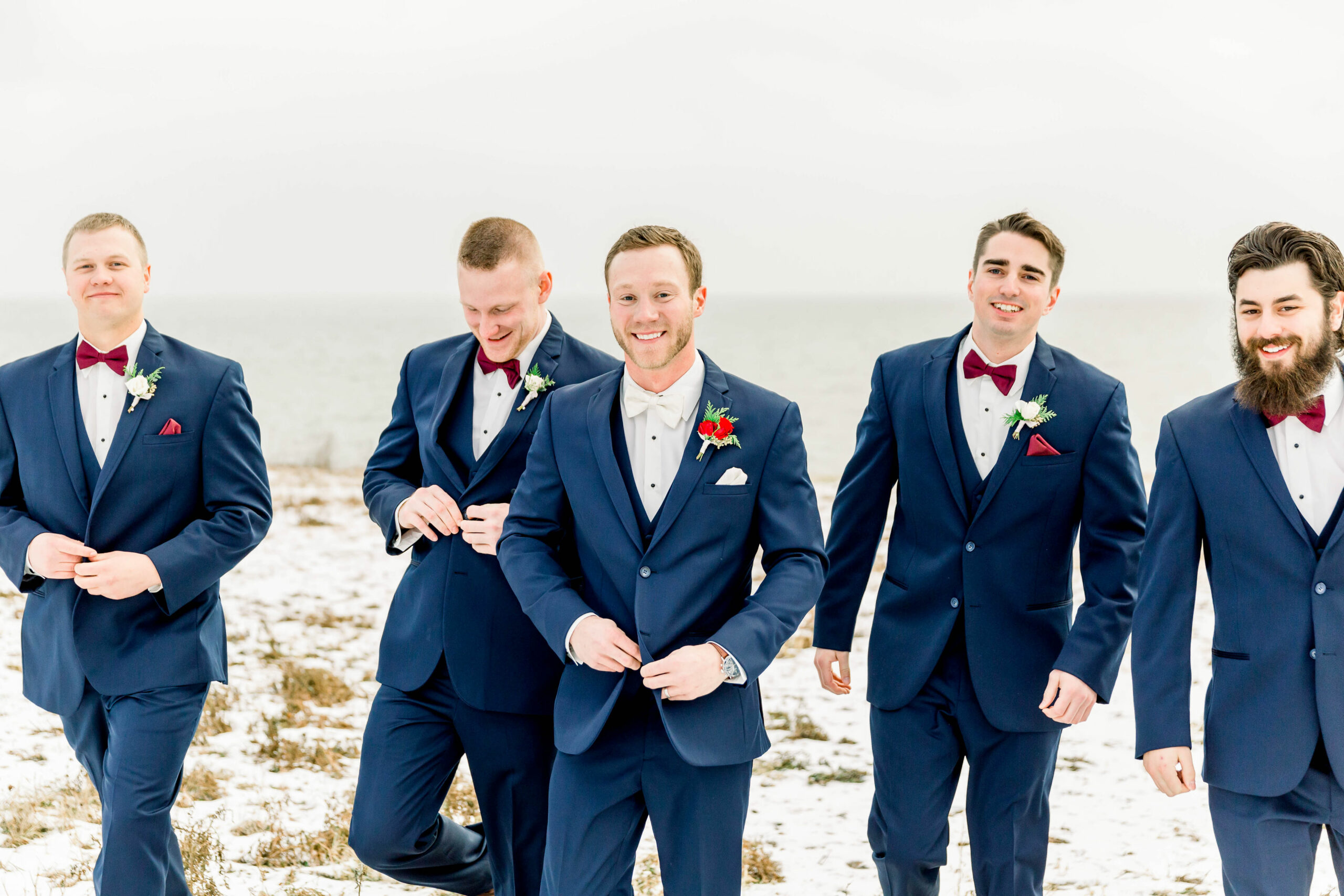 groom and groomsmen walking towards the camera in a field covered in snow. Men wearing navy blue suits with matching vests and red cranberry colored bow ties.