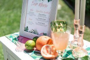 Tropical drinks, fruit, menu on table in sun. Trending Wedding Bar Ideas