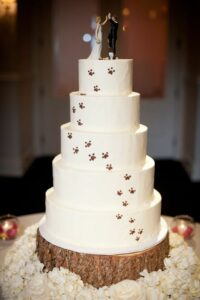 wedding cake with paw prints going up, wedding cake toppe of bride and groom high fiving, dog sitting next to them