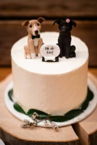 wedding cake with 2 dog toppers with a sign that reads we do too