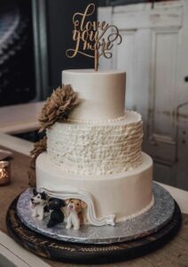 wedding cake with 3 dogs peeking out of icing