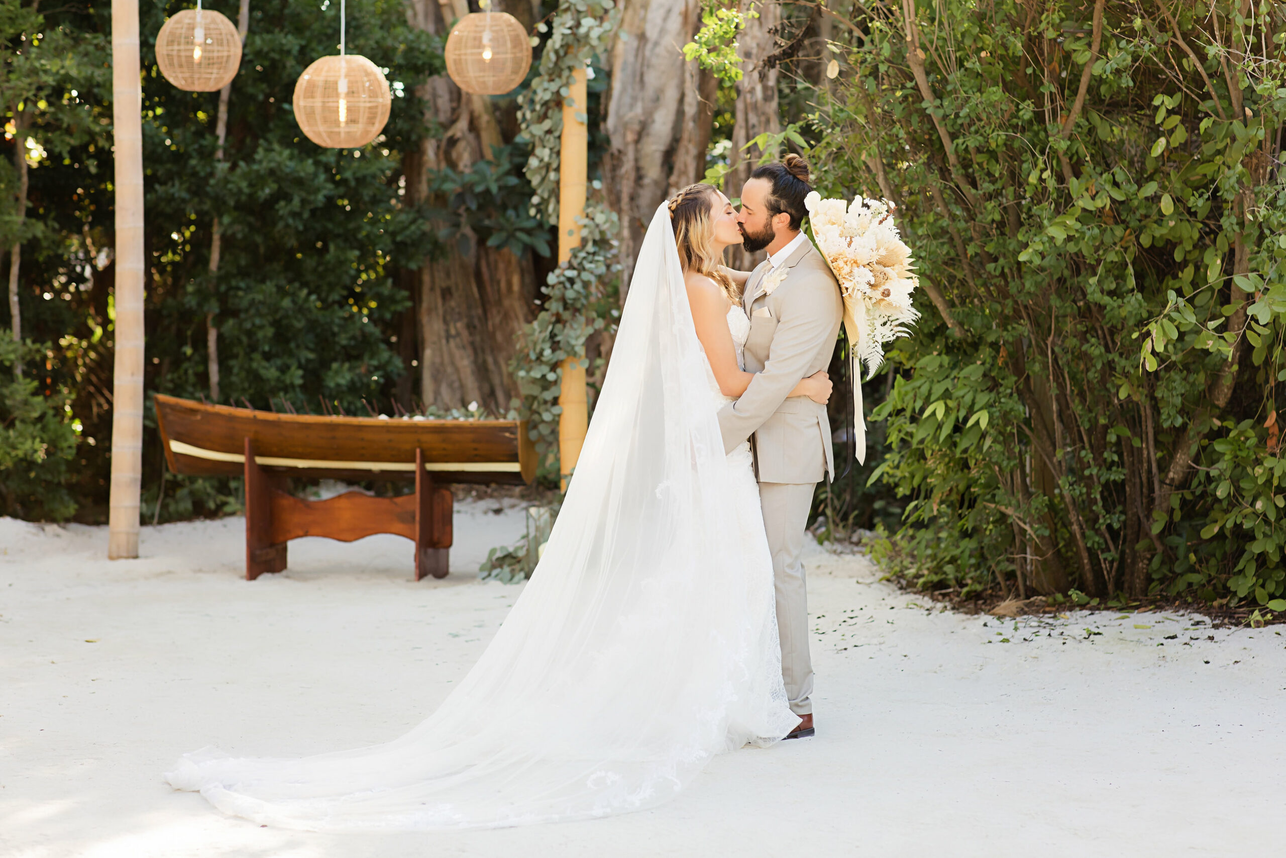 bride in white dress and groom in tan suit kissing on beach