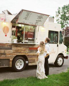 Bride and groom standing in front of food truck. Trending Wedding Ideas.
