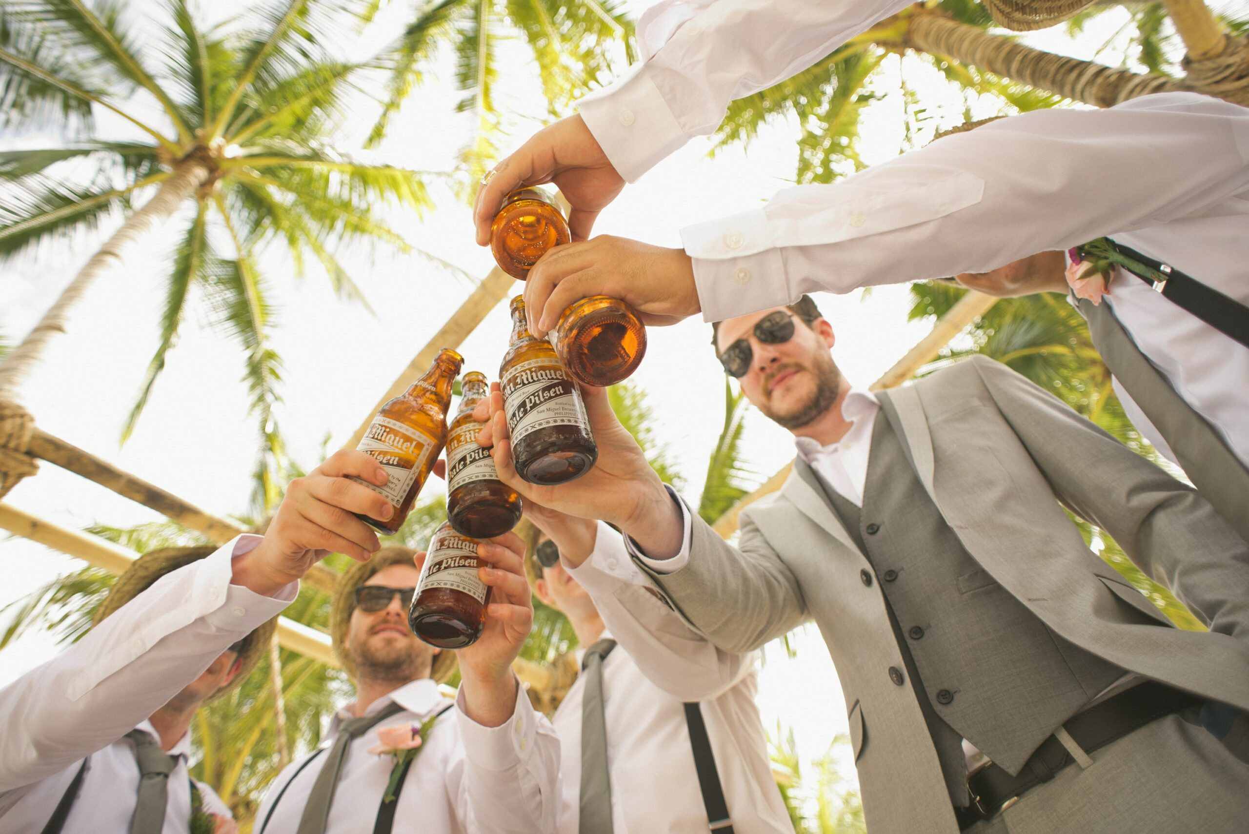 group of guys raising a toast at a summer wedding