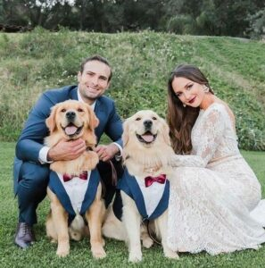 bride and groom with two dogs wearing tuxedo